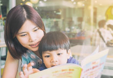 Asian mother is reading her son an educational book. Royalty Free Stock Images