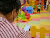 Asian mother`s hand holding and using a smartphone ignoring her little baby playing at a playground stock images
