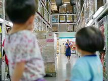 Asian mother shopping for snacks in a cash and carries for her babies royalty free stock images