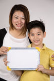 Asian mother and son with blank white board and looking camera Royalty Free Stock Images