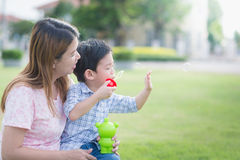 Asian mother and son blowing bubbles Stock Photography