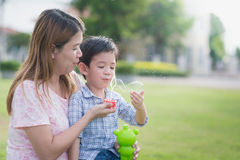 Asian mother and son blowing bubbles Royalty Free Stock Images