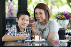 Asian mother with son eating cake in living room Royalty Free Stock Photo