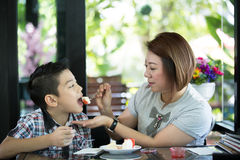 Asian mother with son eating cake in living room Stock Image