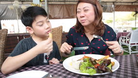 Asian mother with son eating lunch at home stock footage