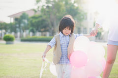Asian mother and son holding hand together and walking Stock Images