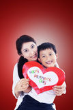 Asian mother and son holding love card on red Royalty Free Stock Images