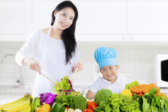 Asian mother and son make salad. Photo of a young Asian mother and her son make vegetables salad in the kitchen at home Royalty Free Stock Photo