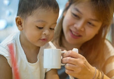 Asian mother and son. The mother was raised a white cup of water. His son drinking the water Royalty Free Stock Photo