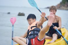 Asian mother and son playing kayaking on the sea during vacation when kid losing balance stock photos