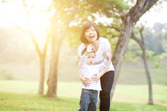 Asian mother and son playing at outdoors. Mother and son are hugging and having fun outdoor in nature. Family outdoor fun, morning with sun flare Royalty Free Stock Photos