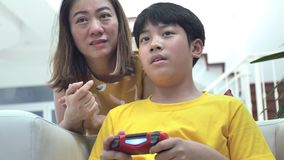 Asian mother and son playing video game at home together.4K Slow motion. Asian mother and son are playing video game at home together.4K Slow motion stock video