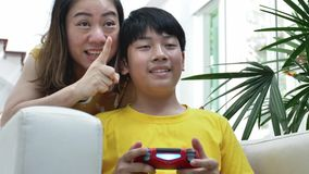 Asian mother and son playing video game at home together.Slow motion. Asian mother and son are playing video game at home together.4K Slow motion stock footage