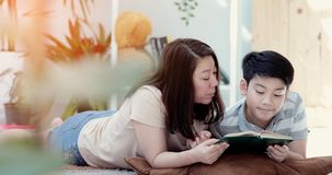 Asian mother with son reading book together with smile face. Happy Asian mother with son reading book together with smile face. in the living room. Mom teaches stock images