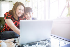 Asian Mother And Son Sitting At Desk Using Laptop At Home Royalty Free Stock Image