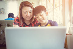 Asian Mother And Son Sitting At Desk Using Laptop At Home Royalty Free Stock Photography