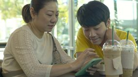 Asian mother and son watching on mobile phone together with smile face. stock footage