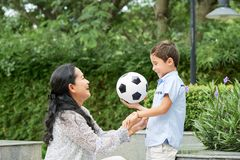 Asian mother supporting son with ball. Side view of cheerful Asian women supporting cute boy with football ball while spending time in beautiful park together stock image