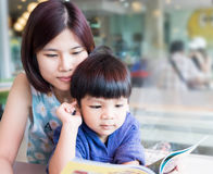 Asian Mother is teaching her son to read Stock Photo