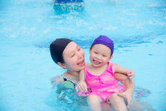 Mother teaching little daughter to swimming in pool Stock Photo