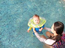 Asian Mother training for infant baby boy in swimming suit floating in pool with safety by baby neck floats.  stock photos