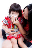Asian mother wipes snot her daughter on white background Stock Photography