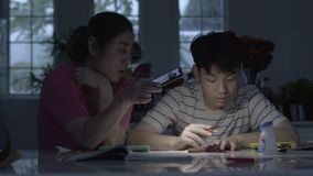 Asian mothers Helping my son do art using the phone light To finish the job. stock video