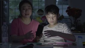 Asian mothers Helping my son do art using the phone light To finish the job. stock video footage