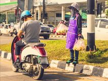 An Asian motorcyclist man in. Helmet and street seller girl withwith packages in hands is waitting for a buyer stock image