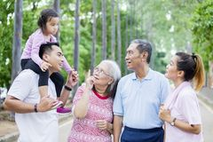 Asian multi generation family chatting in the park. Picture of Asian multi generation family chatting together while standing in the park stock image