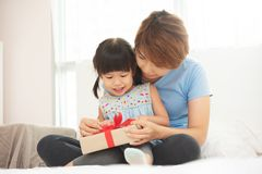 Asian Mum and girl smiling and hugging on bed royalty free stock photography