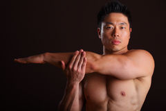 Asian Muscular Man Stretching Left Arm Stock Photography