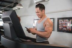 Asian muscular man on treadmill holding smartphone stock photos