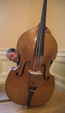 Asian Musician with his Upright String Bass. Asian man peeking around his instrument, a String Upright Bass, having fun hiding Royalty Free Stock Images