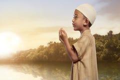 Asian muslim boy with traditional dress praying Stock Image