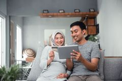 Muslim couple buy and do payment using credit card. Asian muslim couple buy and do payment using credit card while online shopping on market place stock photography