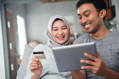Muslim couple buy and do payment using credit card. Asian muslim couple buy and do payment using credit card while online shopping on market place stock images