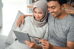 Muslim couple buy and do payment using credit card. Asian muslim couple buy and do payment using credit card while online shopping on market place royalty free stock images