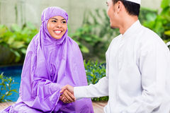 Asian Muslim couple, man and woman, praying at home Royalty Free Stock Photography