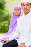 Asian Muslim couple, man and woman, praying at home Stock Photos