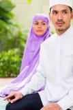 Asian Muslim couple, man and woman, praying at home Stock Photos