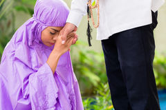 Asian Muslim couple, man and woman, praying at home Stock Images