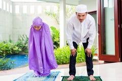 Asian Muslim couple, man and woman, praying at home Royalty Free Stock Photos