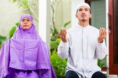 Asian Muslim couple, man and woman, praying at home Stock Photo