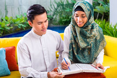 Asian Muslim couple reading together Koran or Quran stock images