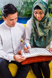 Asian Muslim couple reading together Koran or Quran Royalty Free Stock Images