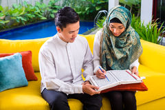 Asian Muslim couple reading together Koran or Quran Stock Photo