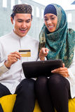 Asian Muslim couple shopping online on pad in living room Royalty Free Stock Photos