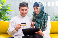 Asian Muslim couple shopping online on pad in living room Royalty Free Stock Photo