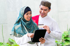 Asian Muslim couple shopping online on pad in living room Stock Photo